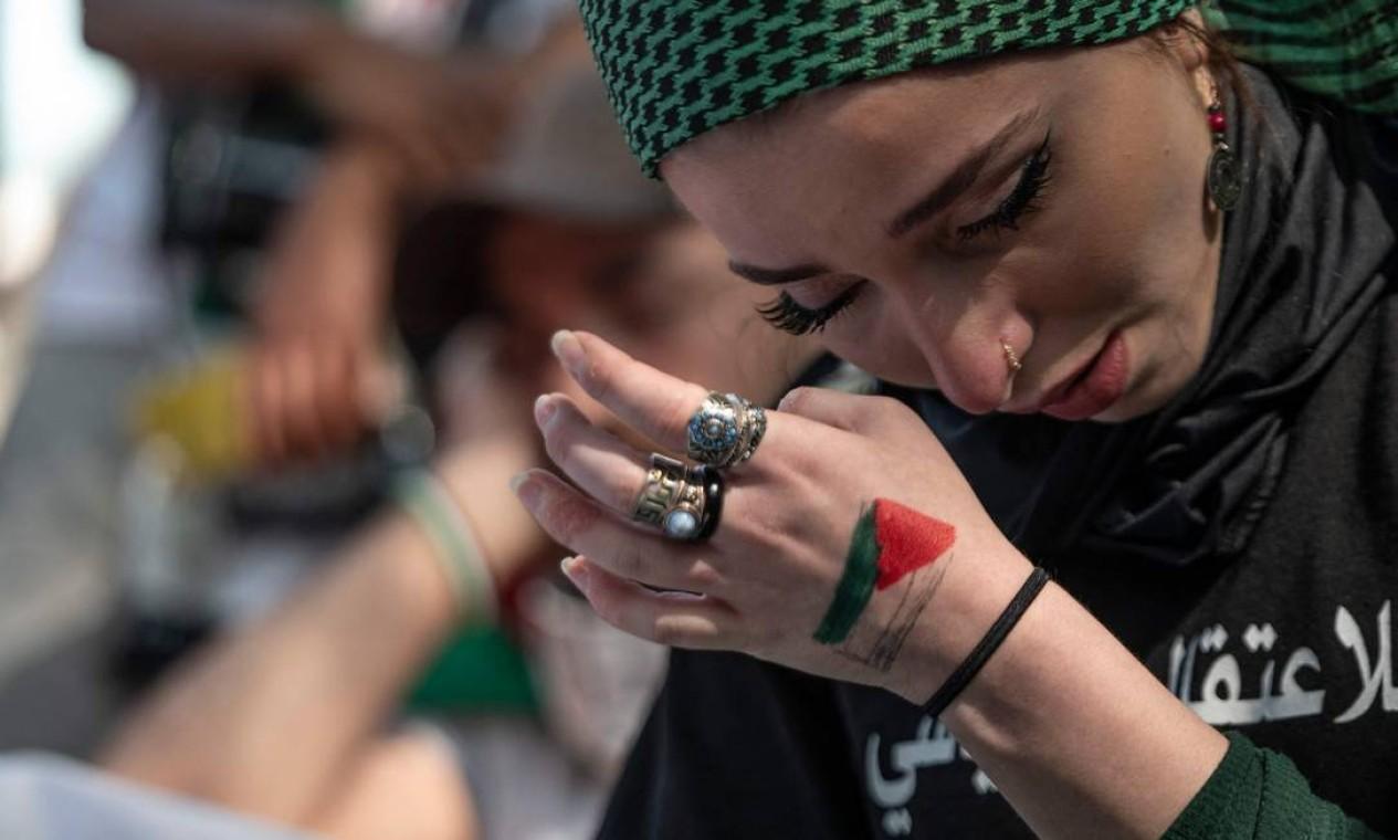 Mulher chora enquanto os nomes das crianças mortas nos recentes combates em Gaza são lidos em voz alta em ato de apoiadores da Palestina em frente à Embaixada de Israel, na capital dos EUA, Washington Foto: ANDREW CABALLERO-REYNOLDS / AFP - 18/05/2021