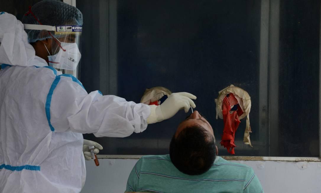 Profissional de saúde coleta esfregaço nasal para teste PCR de Covid-19 para em hospital nos arredores de Siliguri, em maio de 2021 Foto: DIPTENDU DUTTA / AFP