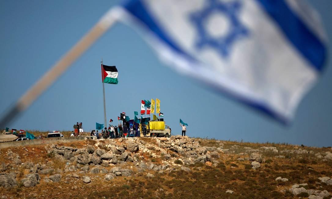As bandeiras de Israel e da Palestina são hasteadas perto de Metula, na fronteira com o Líbano Foto: JALAA MAREY / AFP