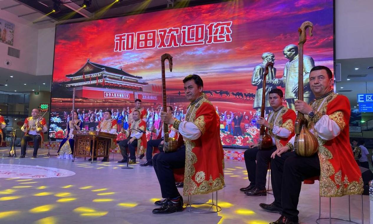 Nos espetáculos de dança uigur, a mensagem oficial é de preservação da cultura tradicional, mas com uma imagem de Mao Tsé-tung ao fundo e músicas do nacionalismo chinês Foto: Marcelo Ninio / Agência O Globo