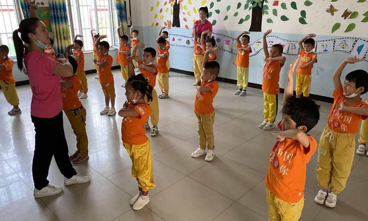 """Crianças uigures são mostradas como exemplo de harmonia étnica em escolas-modelo. Nas camisetas, a frase """"Eu amo a China"""" Foto: Marcelo Ninio / Agência O Globo"""