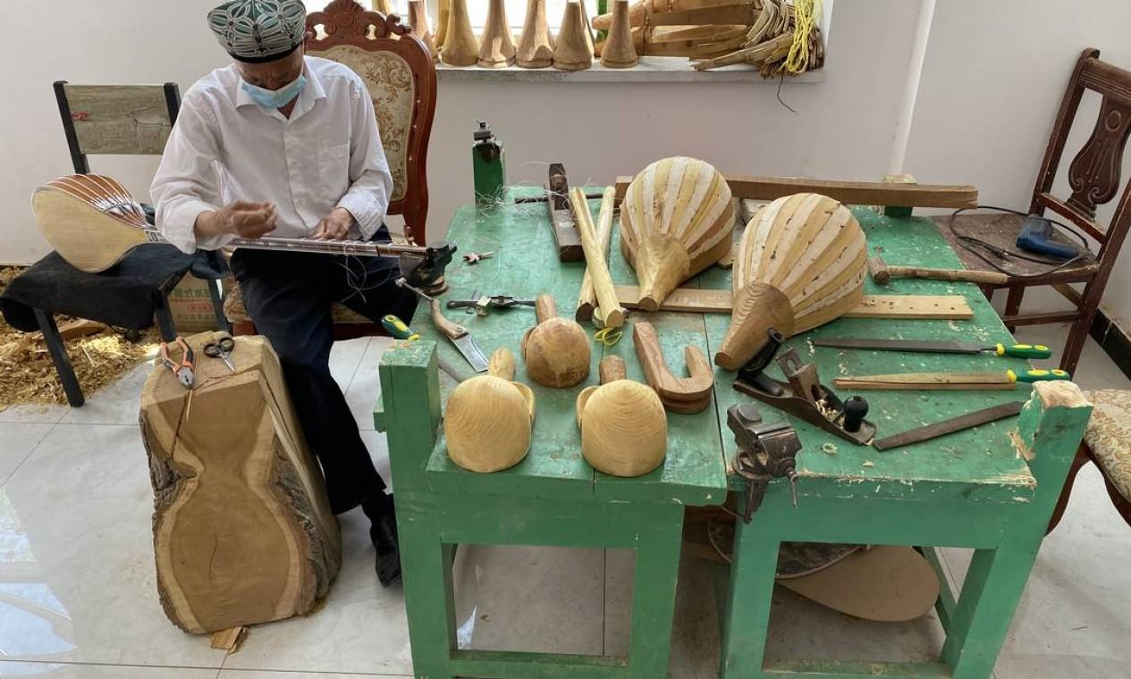 Homem trabalha na fabricação de instrumentos musicais uigures, em Kashgar, Xinjiang Foto: Marcelo Ninio / Agência O Globo