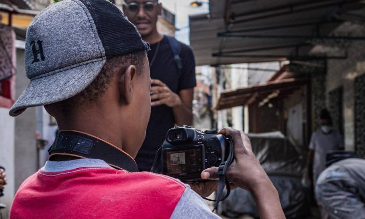 Menino registra mutirão dos artistas de rua em câmera fotográfica profissional Foto: Lenon Felício / LabJaca