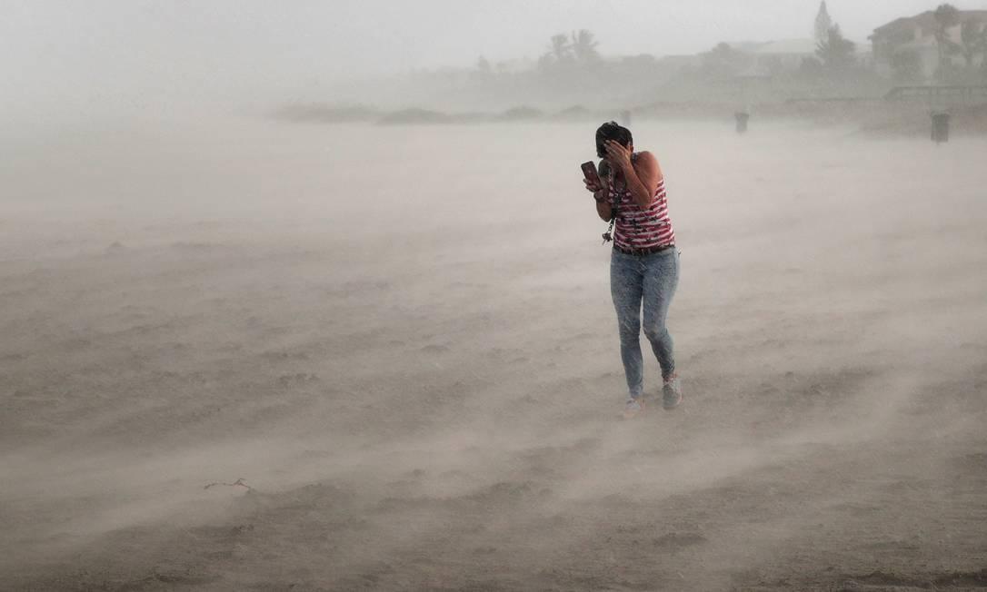 Mulher busca abrigo de vento e chuva com a aproximação do furacão Dorian, na Flórida (EUA), em 2019 Foto: SCOTT OLSON / AFP