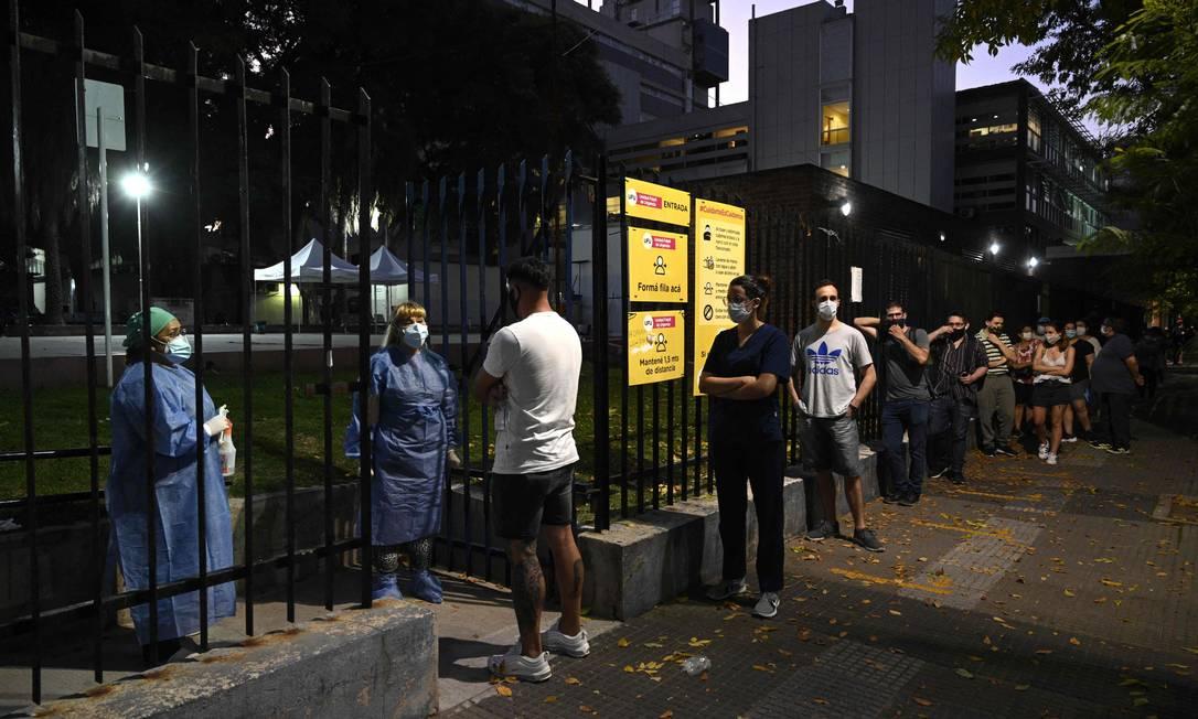 Pessoas com sintomas do novo coronavírus aguardam para serem testadas do lado de fora de hospital em Buenos Aires Foto: JUAN MABROMATA / AFP