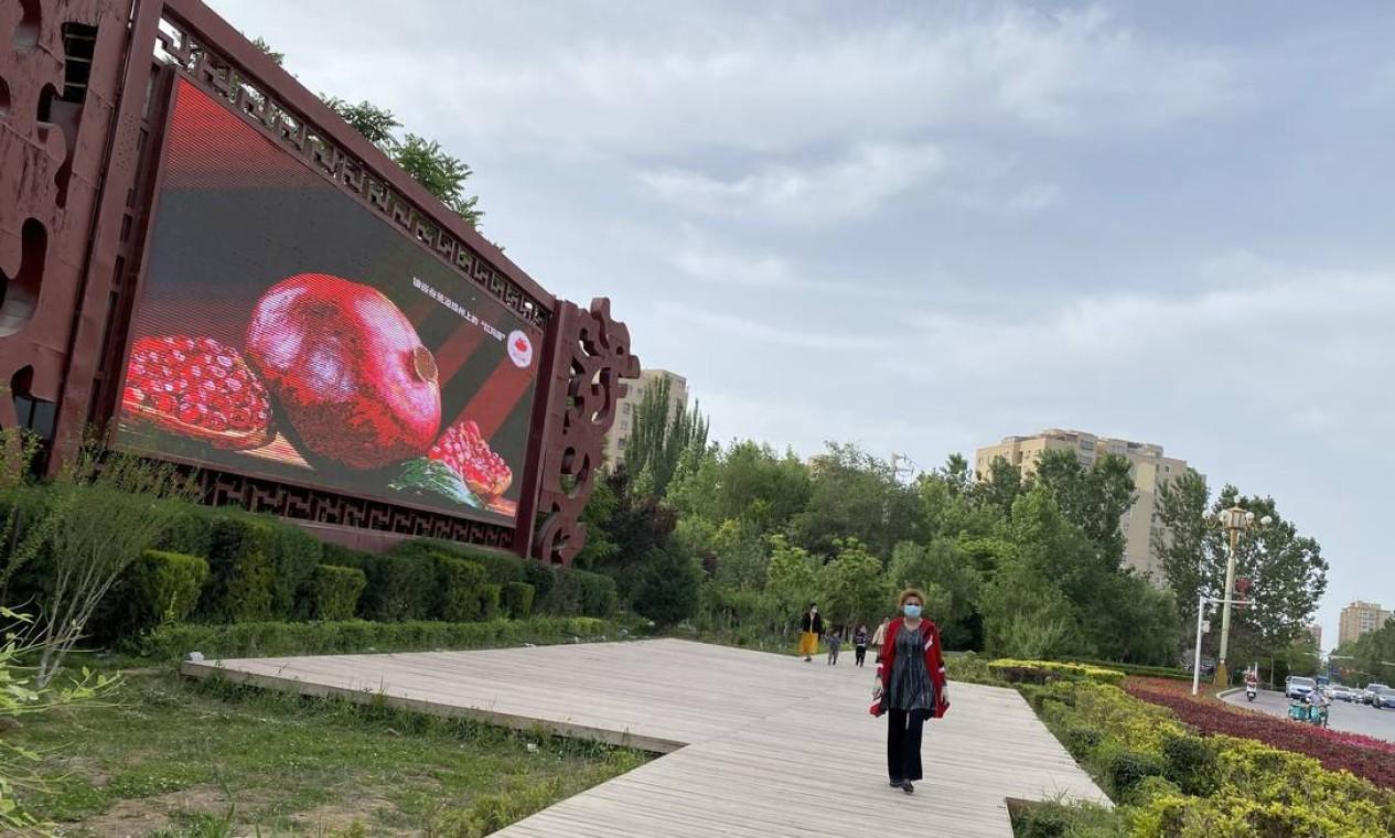 Painel do governo, em Hotan, com imagem de uma romã, símbolo usado pelo presidente Xi Jinping da unidade entre as etnias Foto: Marcelo Ninio / Agência O Globo