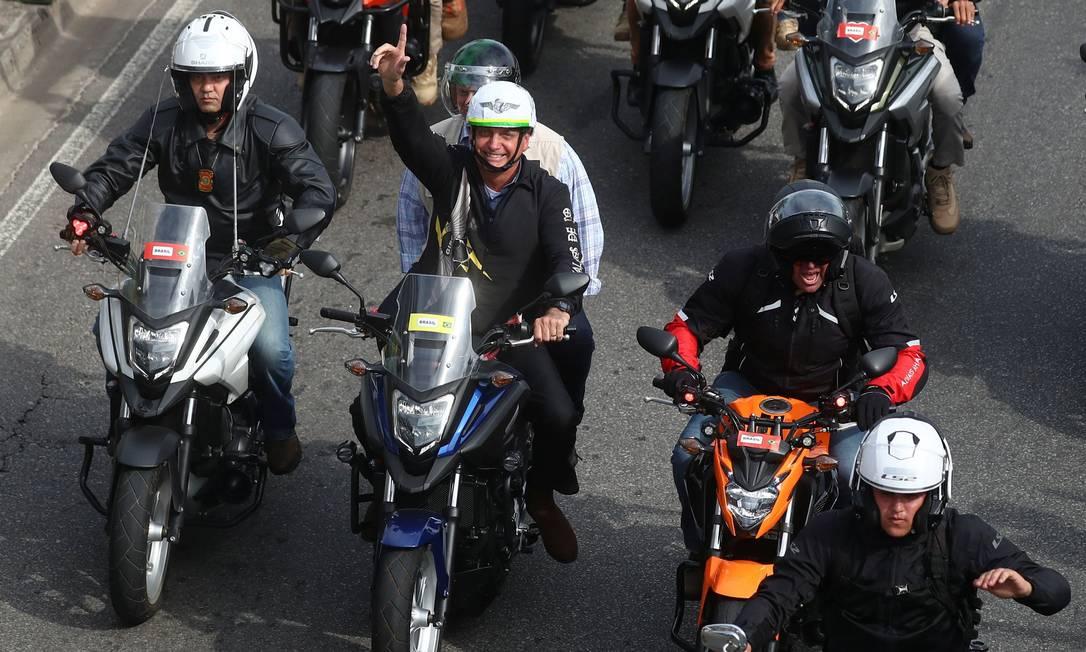 Bolsonaro acena para seus apoiadores enquanto lidera uma carreata, em meio à pandemia, no Rio Foto: PILAR OLIVARES / REUTERS