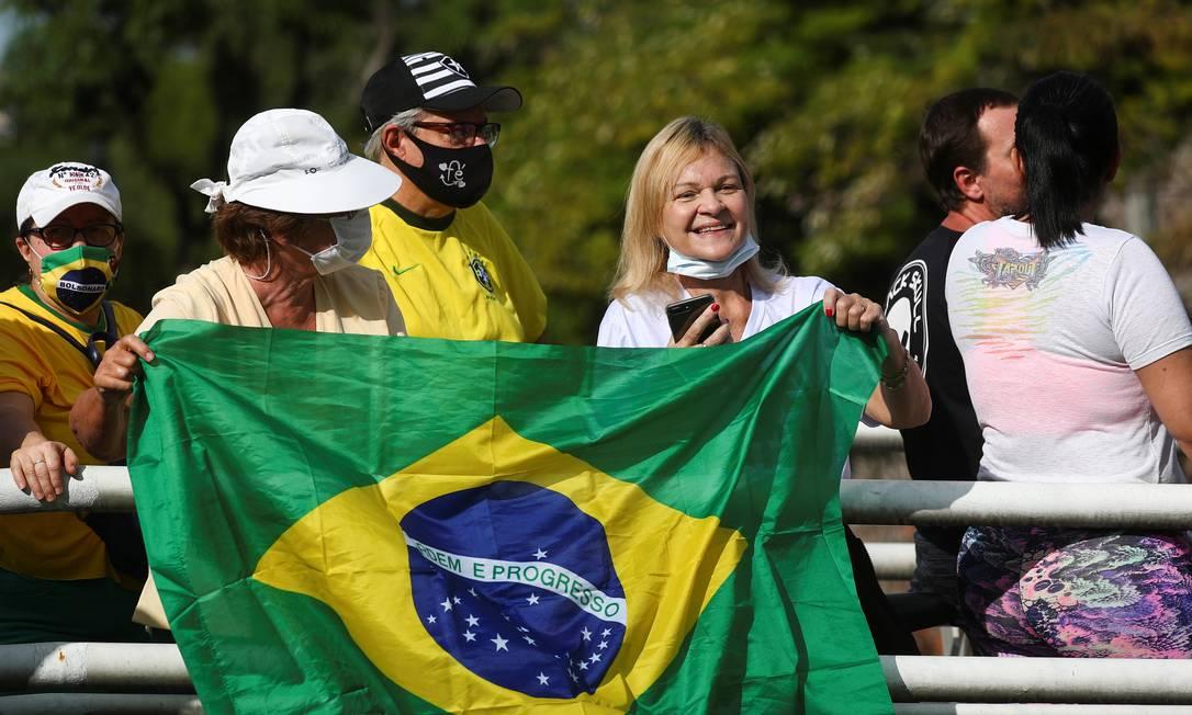 """Apoiadores seguram uma bandeira nacional enquanto esperam para ver a passagem do presidente à frente de sua """"motociata"""" Foto: PILAR OLIVARES / REUTERS"""