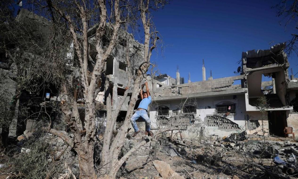 Menino palestino brinca ao lado dos escombros de casa que destruída por ataques aéreos israelenses no início deste mês, em Beit Hanoun, no norte da Faixa de Gaza Foto: Mahmud Hams / AFP