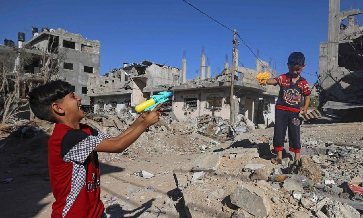 Crianças palestinas brincam com armas de brinquedo em Beit Hanoun, bairro da Faixa de Gaza, que foi bombardeado por Israel, depois da vigência de um cessar-fogo com o grupo Hamas Foto: Mahmud Hams / AFP