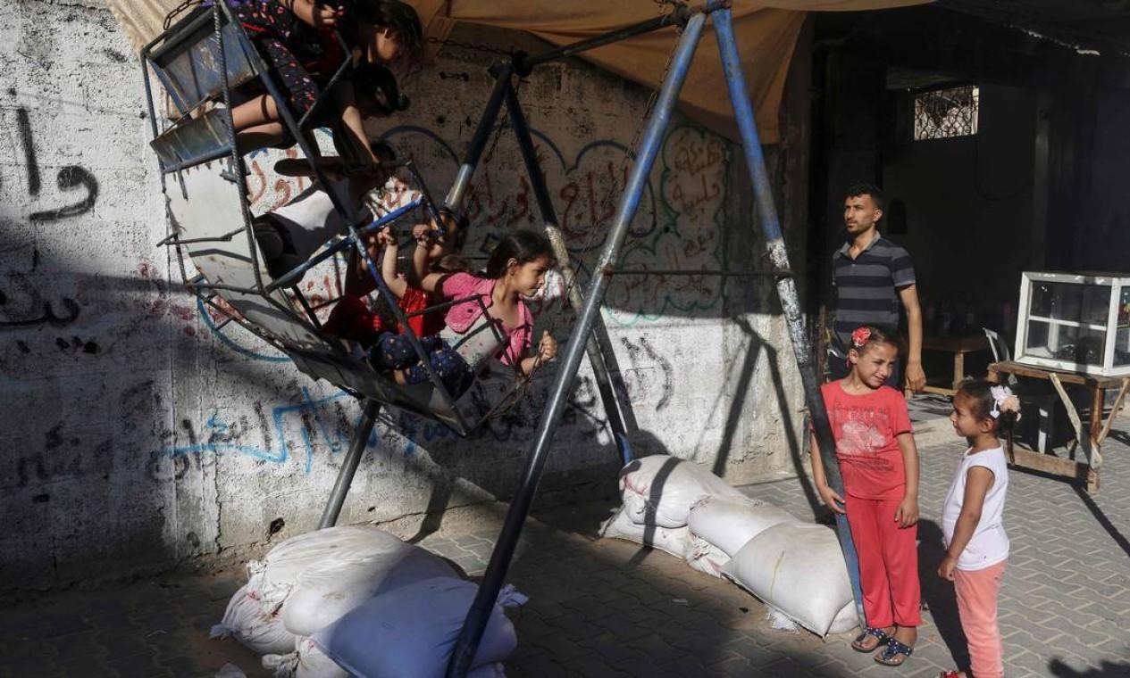 Um palestino vigia crianças brincando em um balanço, em Beit Hanoun, no norte da Faixa de Gaza, alvo de ataques israelenses Foto: Mahmud Hams / AFP