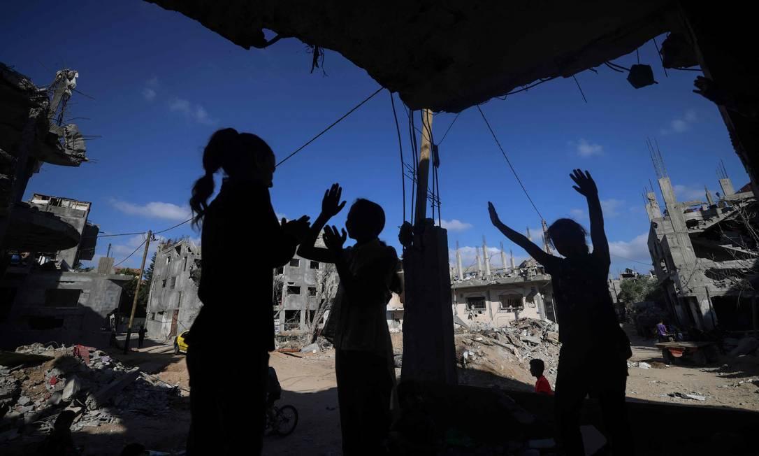 Crianças palestinas brincam ao lado de edifícios fortemente danificados por ataques aéreos Israelenses à Faixa de Gaza Foto: Mahmud Hams / AFP
