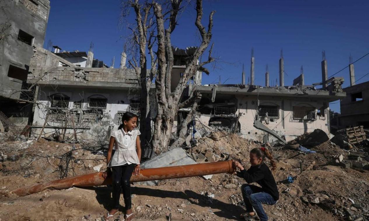 Meninas palestinas brincam ao lado de um cano de esgoto em meio aos escombros de casas destruídas Foto: Mahmud Hams / AFP