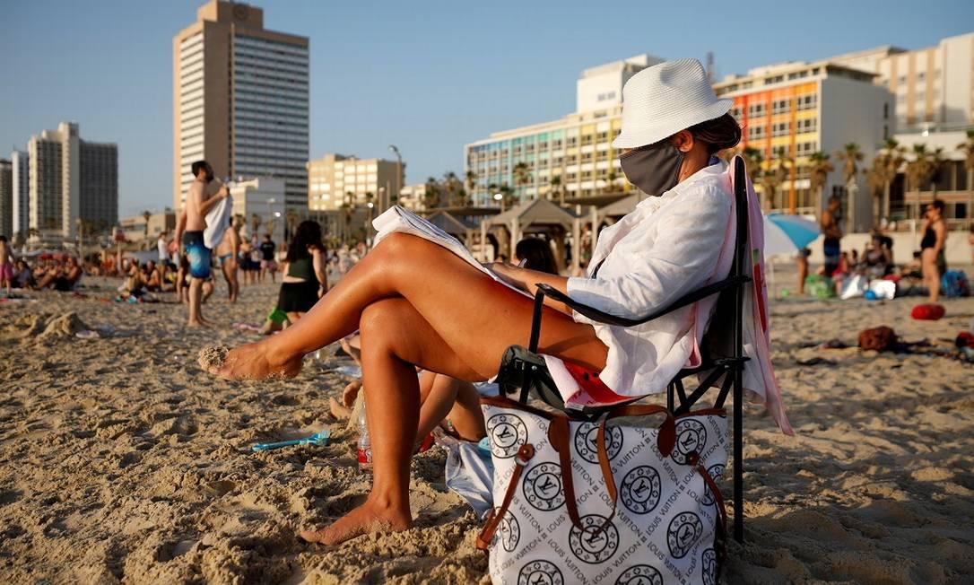 Banhista de máscara aproveita a praia em Tel Aviv, em Israel Foto: Amir Cohen / REUTERS