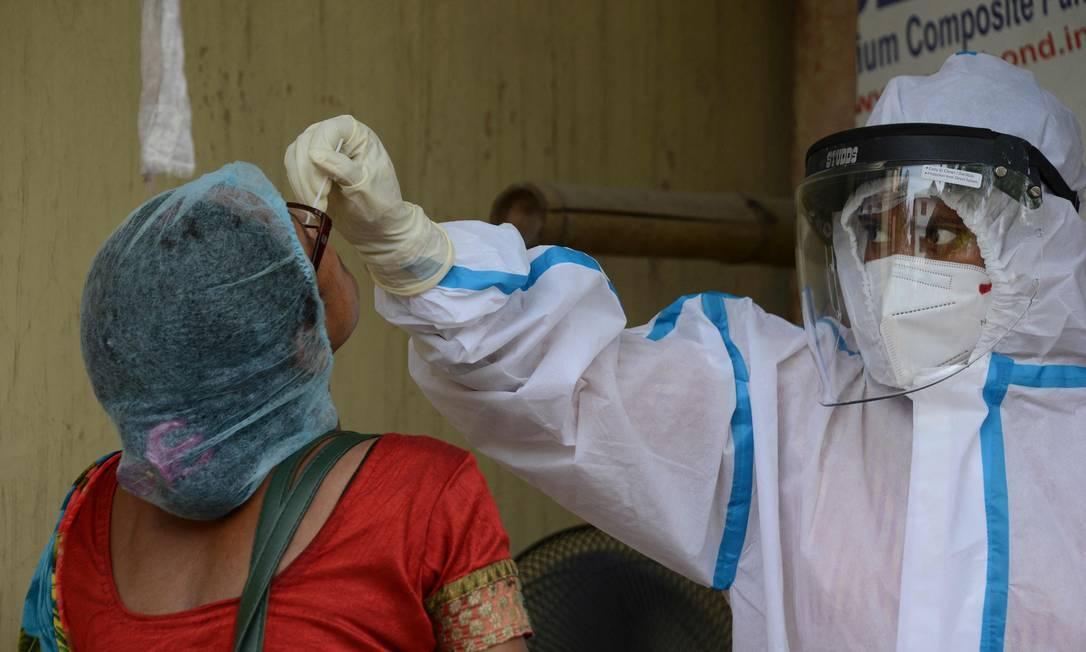 Profissional de saúde coleta uma amostra de esfregaço de uma mulher para teste de Covid-19 em um centro de saúde primário em Siliguri em 24 de maio de 2021 Foto: DIPTENDU DUTTA / AFP