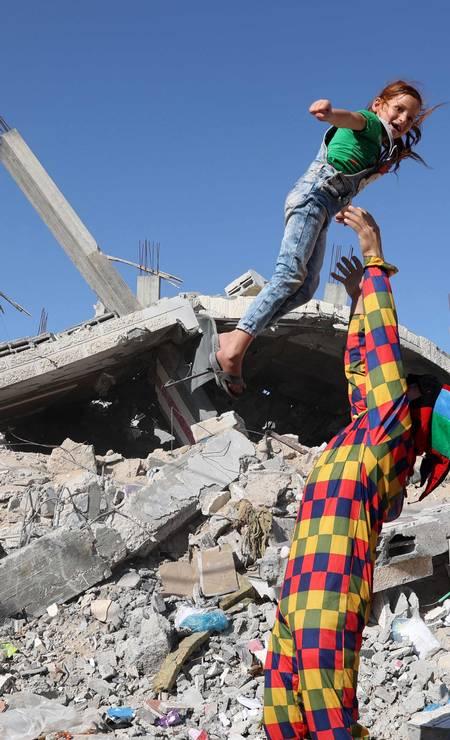 Palestino vestido de palhaço entretém uma criança em meio às ruínas de um prédio em Rafah, no sul da Faixa de Gaza Foto: SAID KHATIB / AFP
