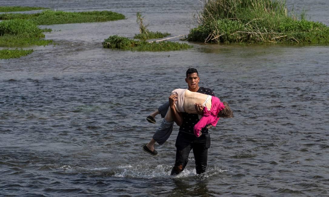 Um migrante venezuelano cruza o rio Grande, na fronteira entre os EUA e o México, carregando uma idosa Foto: GO NAKAMURA / REUTERS