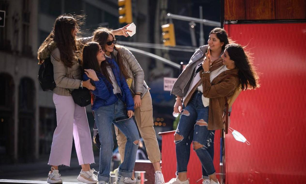 Um grupo de mulheres, sem máscara, posa para fotos na Times Square. Cerca de 50% dos 8,3 milhões de moradores da mais populosa cidade dos EUA já receberam pelo menos uma dose de vacina anticovid Foto: Ed Jones / AFP