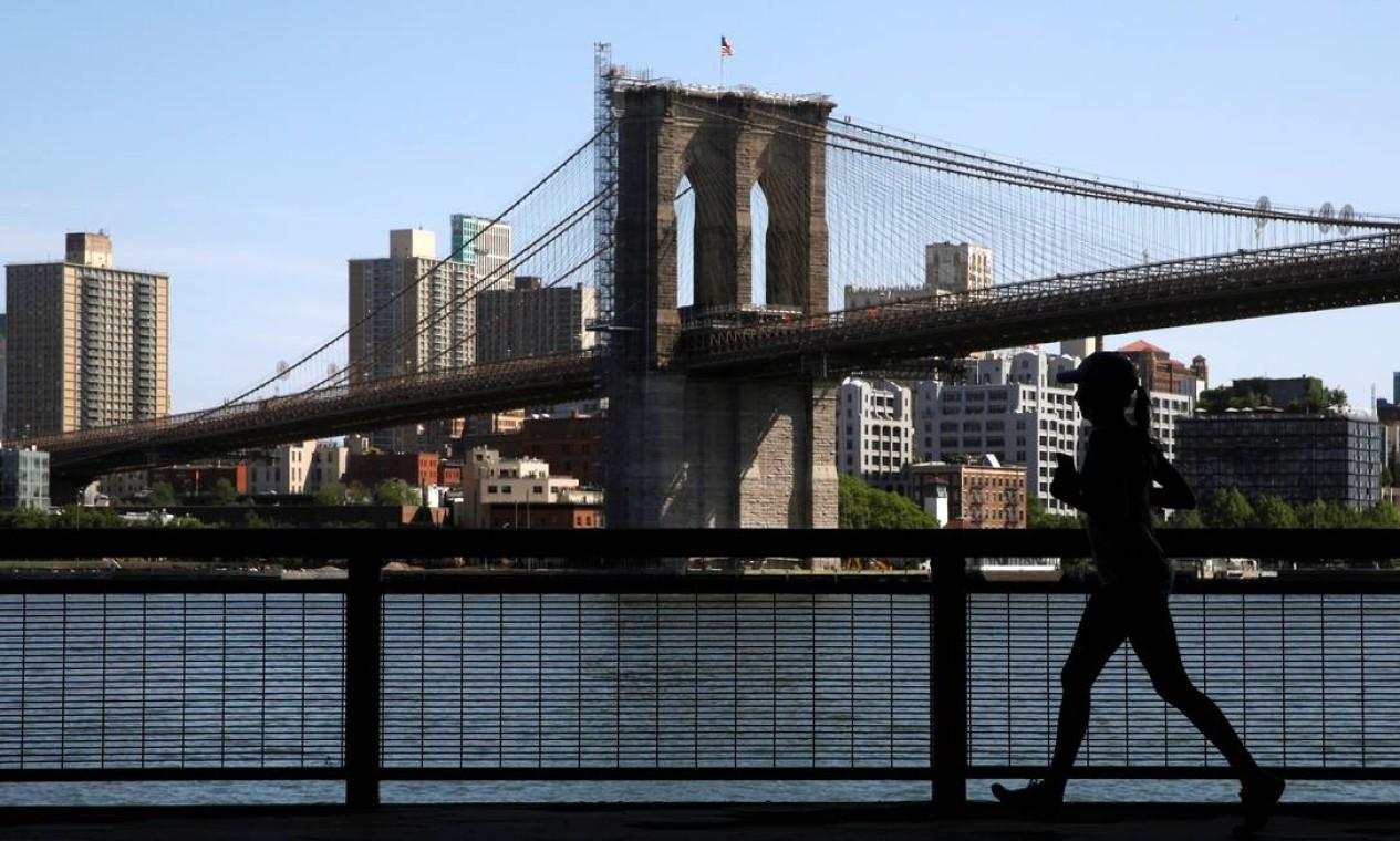 Uma mulher corre ao longo do East River Greenway, perto da Ponte do Brooklyn, na cidade de Nova York. Número de casos de Covid-19 está menor, e mais pessoas estão vacinadas Foto: BRENDAN MCDERMID / REUTERS