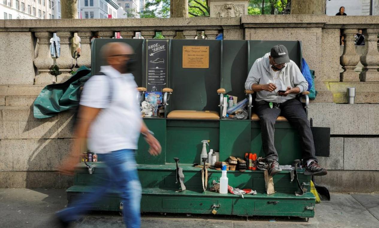 Engraxate espera por clientes em sua barraca. Ao todo, 42% da população da cidade já completaram o ciclo vacinal Foto: ANDREW KELLY / REUTERS
