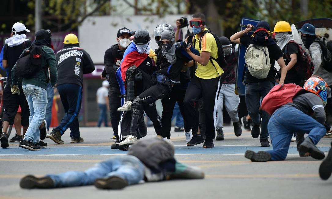 Um homem é ajudado por outros manifestantes após ser atingido durante confrontos com a polícia em protesto em Cali Foto: LUIS ROBAYO / AFP