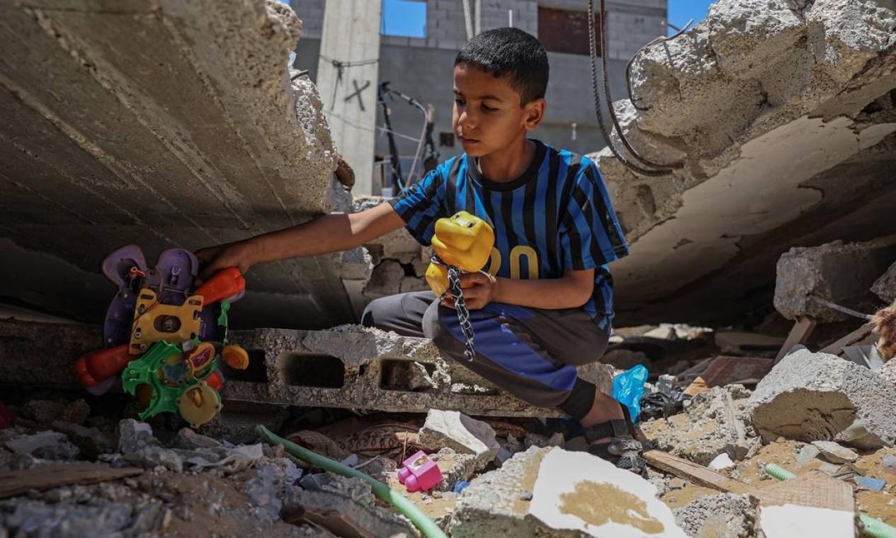 Menino palestino recupera seus brinquedos dos escombros de sua casa, recentemente destruída por ataques israelenses, em Khan Yunis, no sul da Faixa de Gaza Foto: SAID KHATIB / AFP