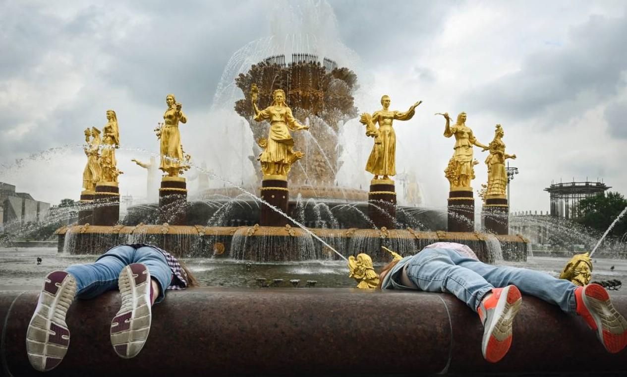 """Crianças tentam tirar moedas da fonte """"Amizade das Nações"""", construída em 1954, simbolizando a amizade das dezesseis repúblicas soviéticas que formam a URSS, no Centro de Exposições de Toda a Rússia (VDNKh), em Moscou Foto: ALEXANDER NEMENOV / AFP"""