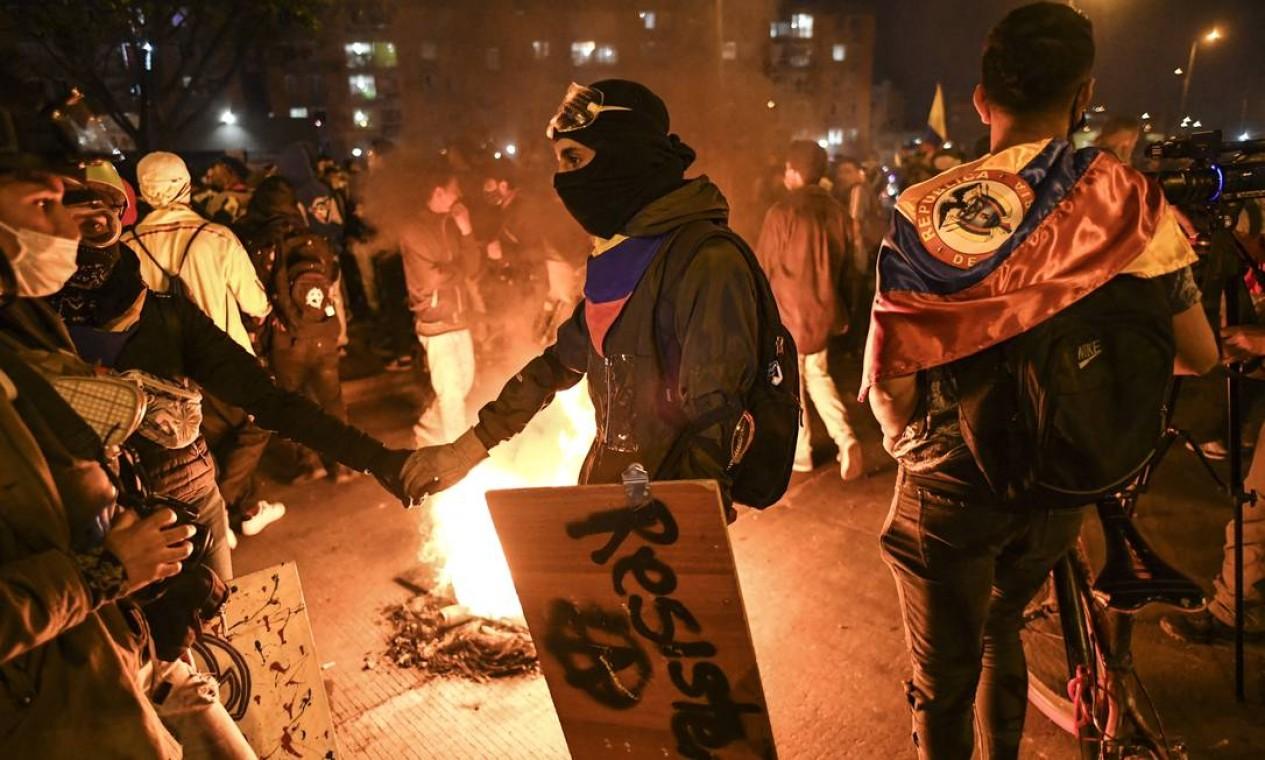 Manifestantes marcham ao redor de uma barricada em chama durante um novo protesto contra o governo do presidente Ivan Duque, em Portal De Las Americas, ao sul de Bogotá Foto: JUAN BARRETO / AFP