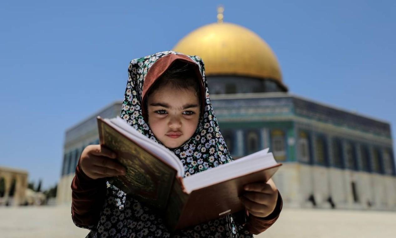 Menina lê um livro sagrado em frente à Cúpula da Rocha, no complexo que abriga a Mesquita de al-Aqsa, conhecida pelos muçulmanos como Santuário Nobre, e pelos judeus, como Monte do Templo, na Cidade Velha de Jerusalém Foto: AMMAR AWAD / REUTERS