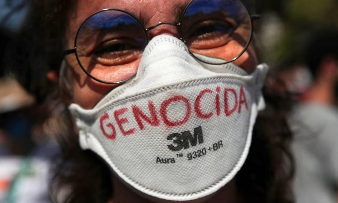Manifestante exibe máscara de proteção com a palavra 'genocida', no Rio Foto: Ricardo Moraes / Reuters