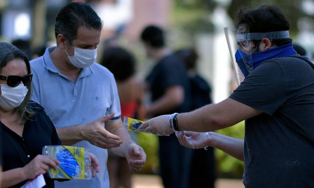 Manifestantes distribuíram máscaras durante o ato na capital mineira Foto: DOUGLAS MAGNO / AFP