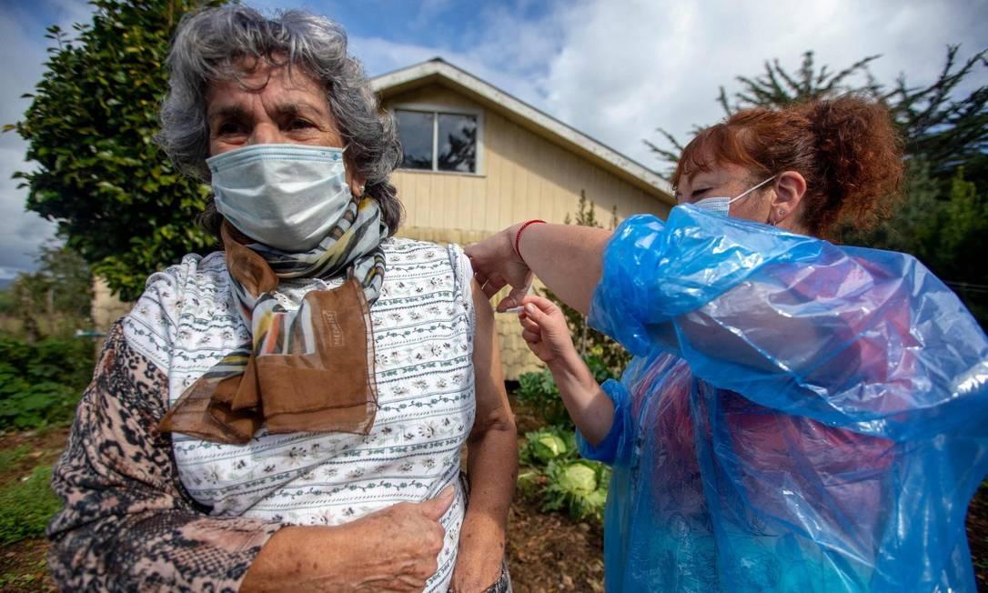 Enfermeira chilena Ximena Ampuero vacina mulher idosa na ilha Chiloe, a cerca de 1.230 km ao Sul de Santiago, no Chile Foto: ALVARO VIDAL / AFP/16-4-21