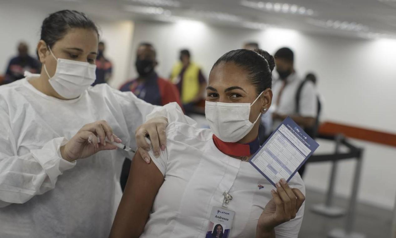 Funcionária de companhia aérea exibe cartão de vacinação contra Covid-19, no Santos Dumont, Centro do Rio. Trabalhadores de aeroportos e do porto começaram a ser imunizados Foto: Márcia Foletto / Agência O Globo - 02/06/2021