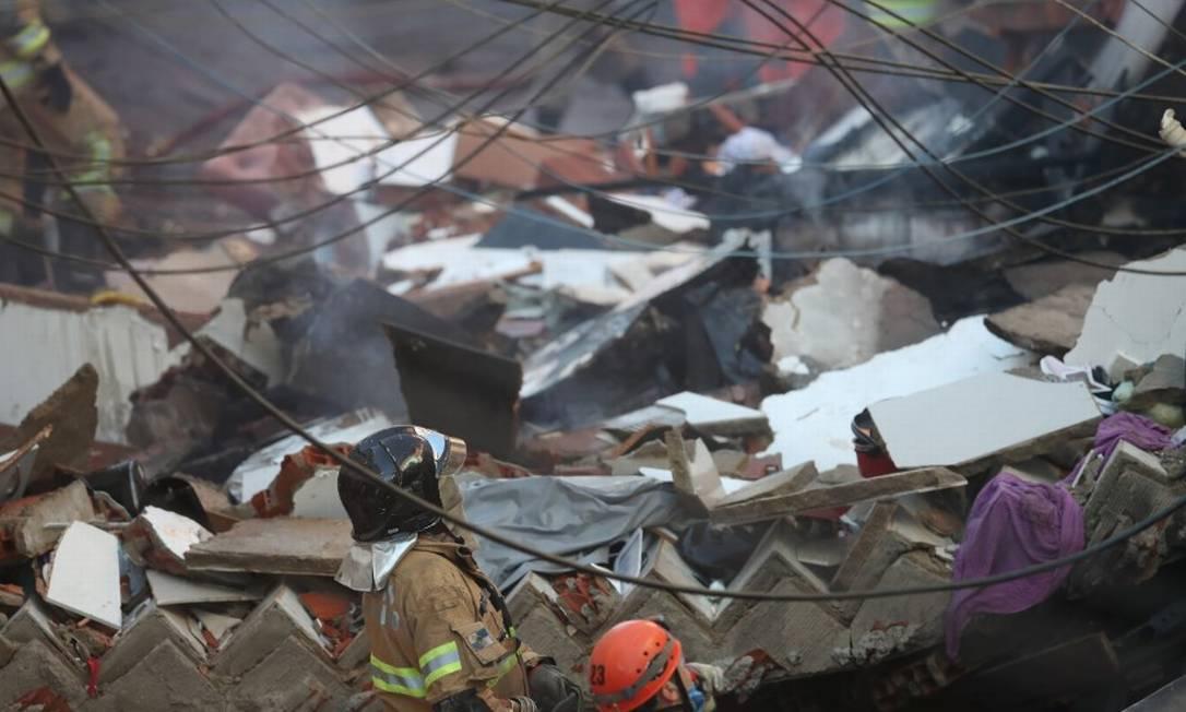 Bombeiros ao lado dos escombros do prédio que caiu em Rio das Pedras Foto: Ricardo Moraes / Reuters