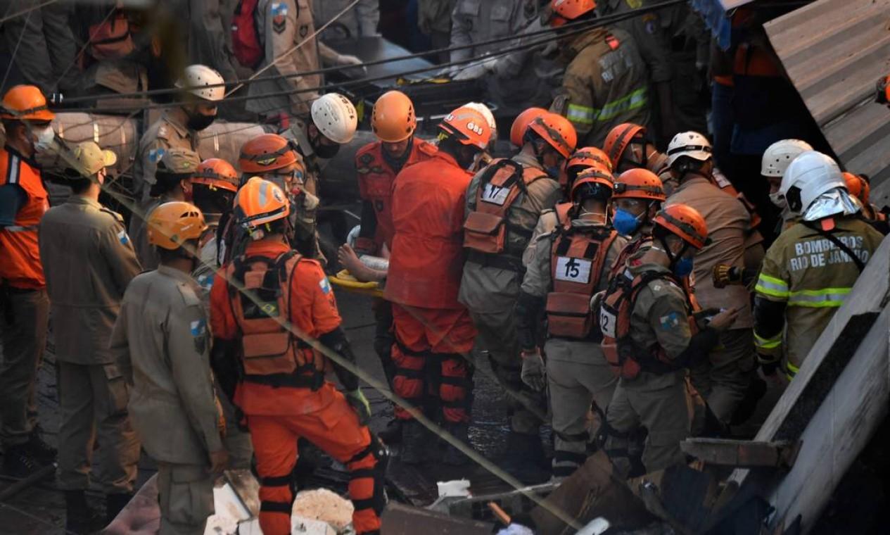Bombeiros conseguem retirar com vida uma vítima do desabamento identificada como Kiara Abreu Foto: MAURO PIMENTEL / AFP