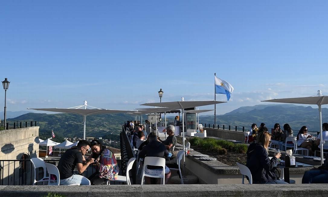 Pessoas sentadas ao ar livre num bar na República de San Marino, que desde maio oferece vacinas contra a Covid-19 a turistas Foto: ALBERTO LINGRIA / REUTERS