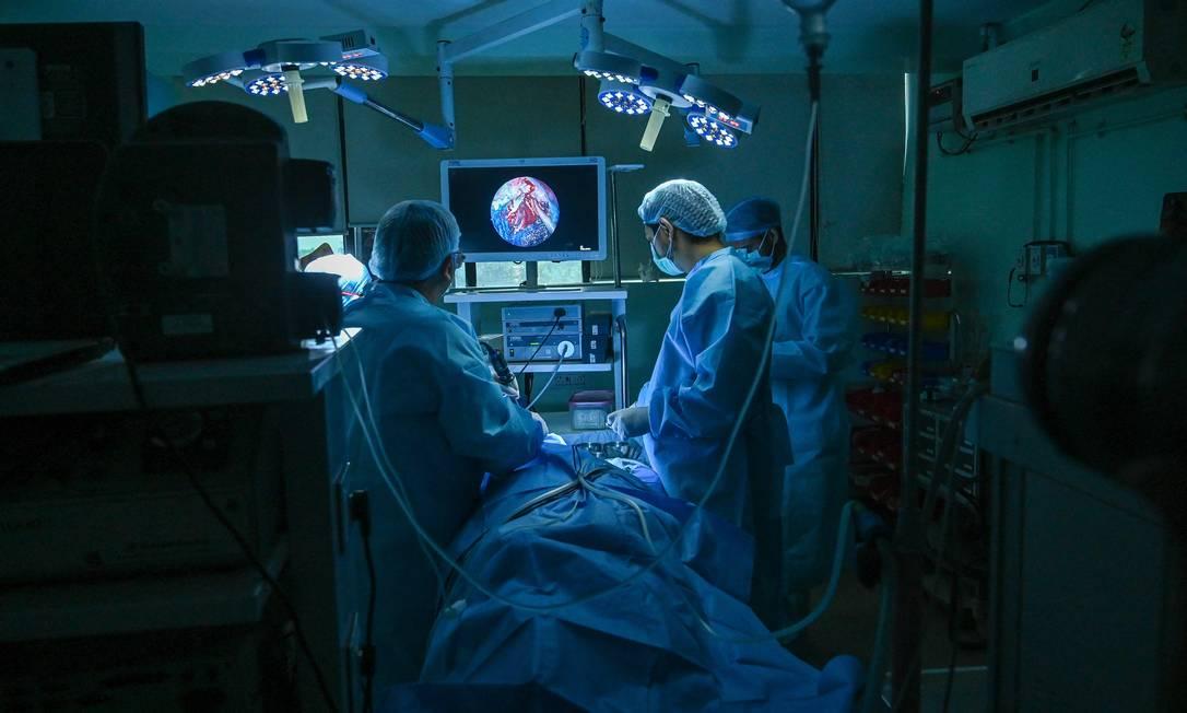 """Médico realiza uma cirurgia para remover o """"fungo preto"""" de um paciente que se recuperou da Covid-19 em um hospital em Ghaziabad, Índia Foto: PRAKASH SINGH / AFP"""