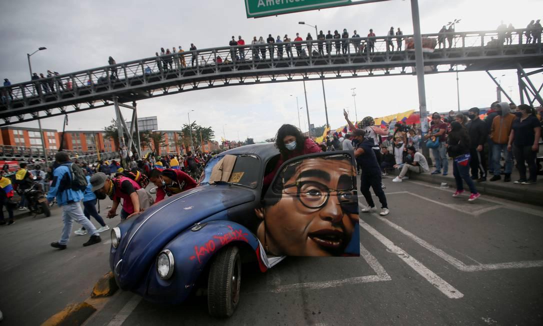 Pessoas empurram um carro com a imagem do falecido humorista e jornalista colombiano Jaime Garzón durante um protesto exigindo ações do governo para enfrentar a pobreza, a violência policial e as desigualdades nos sistemas de saúde e educação, em Bogotá, Colômbia Foto: LUISA GONZALEZ / REUTERS
