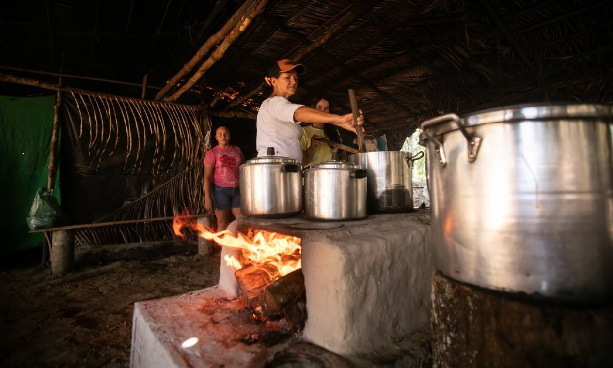Mulheres se dividem no trabalho de preparo do alimento para os assentados Foto: Brenno Carvalho / Agência O Globo