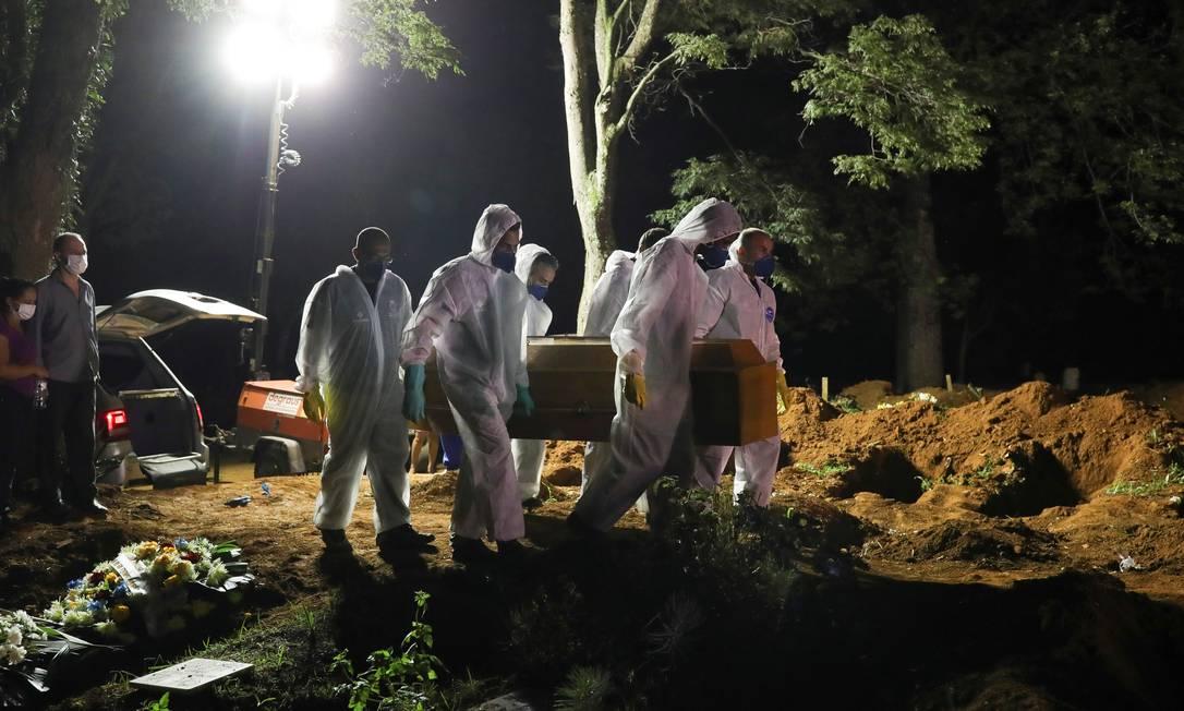 Coveiros com roupas protetoras levam caixão de pessoa morta por Covid-19 no Cemitério Vila Formosa, em São Paulo Foto: AMANDA PEROBELLI/25-3-2021
