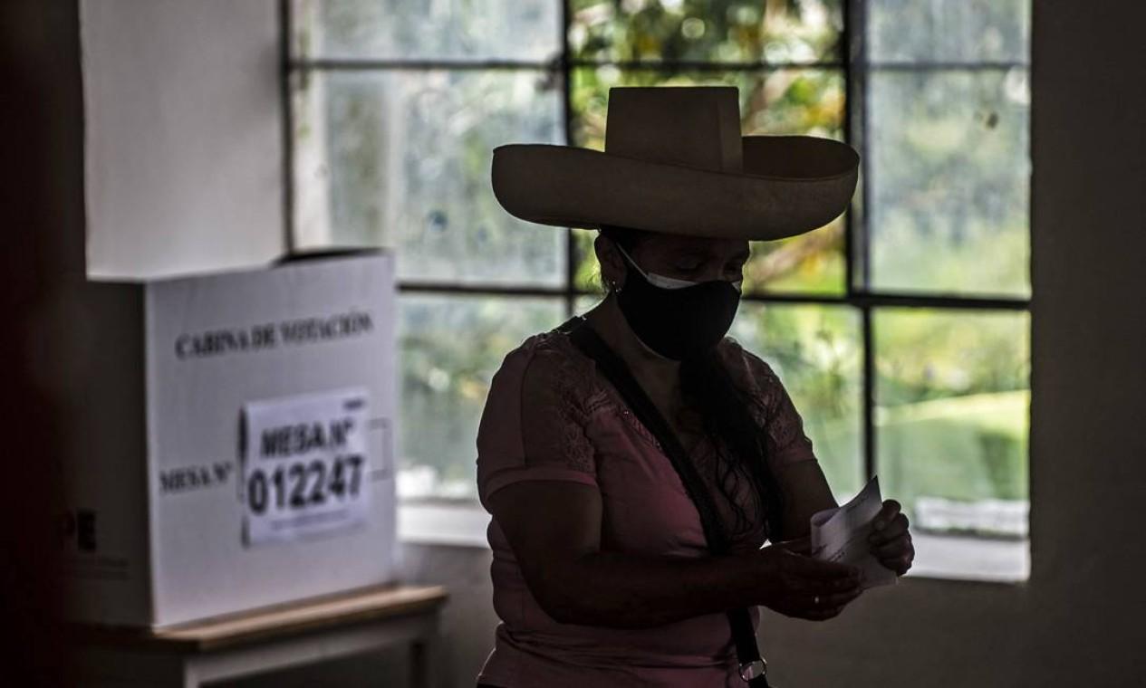 Uma mulher vota em uma seção eleitoral durante as eleições nacionais, em Tacabamba, Peru Foto: ERNESTO BENAVIDES / AFP
