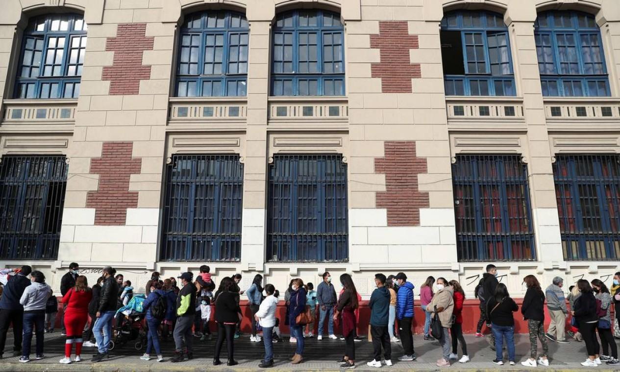 Membros da comunidade peruana que vivem no Chile fazem fila antes de votar em uma seção eleitoral, em Santiago Foto: IVAN ALVARADO / REUTERS