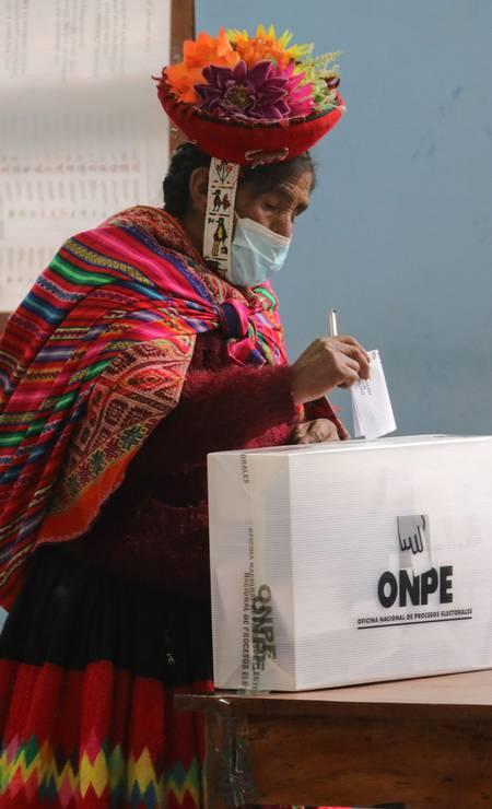 Mulher com traje regional típico lança seu voto em uma urna na comunidade andina de Chinchero, perto de Cusco Foto: STR / AFP