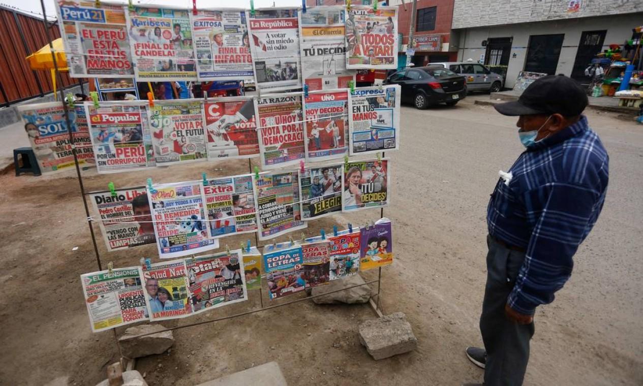 Homem lê as manchetes de jornais locais no dia do segundo turno das eleições. Empatados tecnicamente, candidatos encerraram suas campanhas na última quinta-feira, em Lima, tentando convencer indecisos Foto: GIAN MASKO / AFP