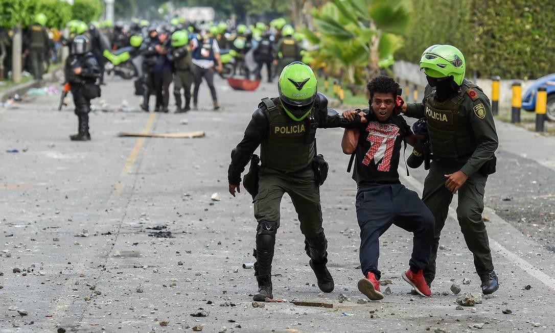 Policiais detêm manifestante durante protesto em Cali, na Colômbia Foto: LUIS ROBAYO / AFP