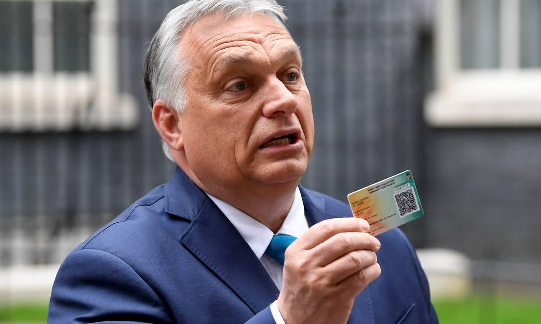 O primeiro-ministro da Hungria, Viktor Orbán, mostra seu cartão de vacinação durante entrevista coletiva em Londres, Reino UNido Foto: TOBY MELVILLE / REUTERS/28-05-2021