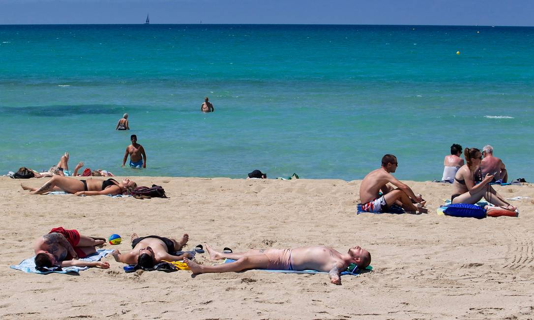 Turistas curtem o sol na Praia de Palma, em Palma de Mallorca, no momento em que a Espanha abre as fronteiras para turistas do mundo inteiro (menos brasileiros e sul-africanos) que já tenham sido totalmente vacinados contra a Covid-19 Foto: JAIME REINA / AFP
