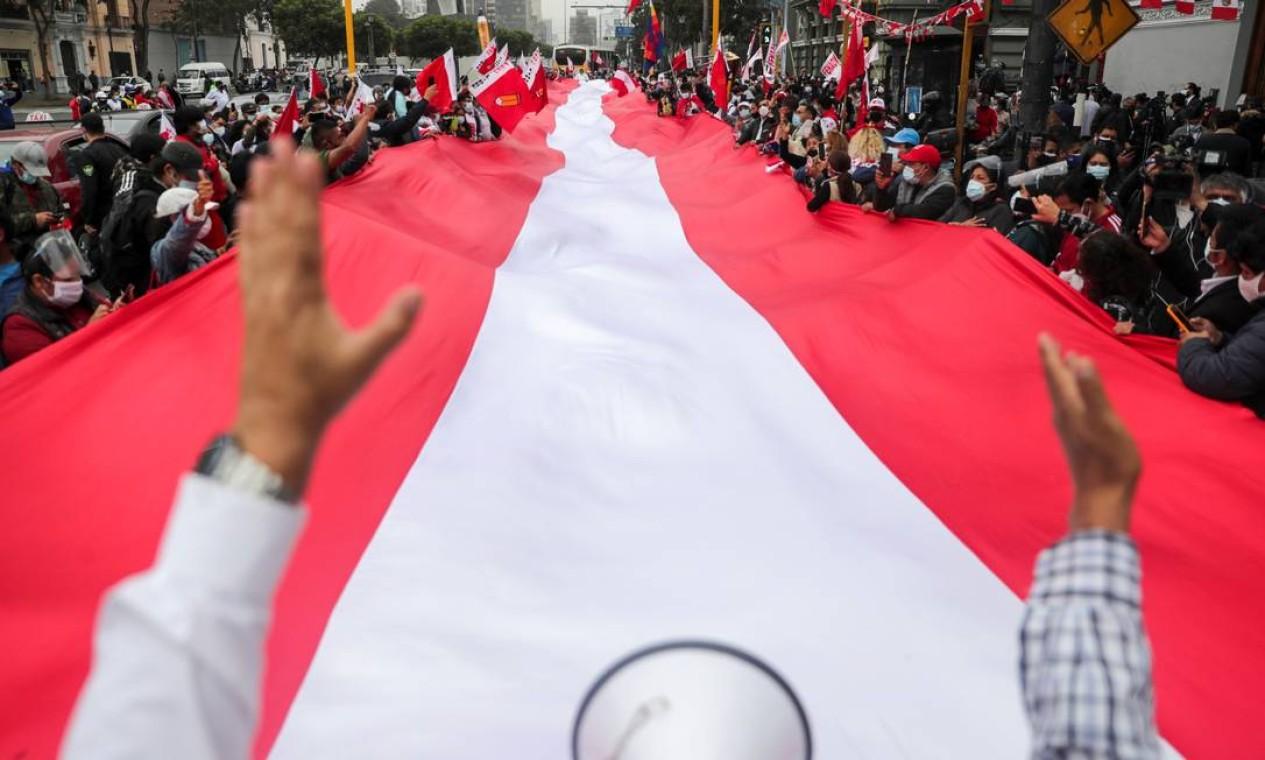 Apoiadores do candidato à presidência do Peru, Pedro Castillo, carregam uma bandeira peruana enorme na rua no dia seguinte ao segundo turno, em Lima, Peru Foto: SEBASTIAN CASTANEDA / REUTERS