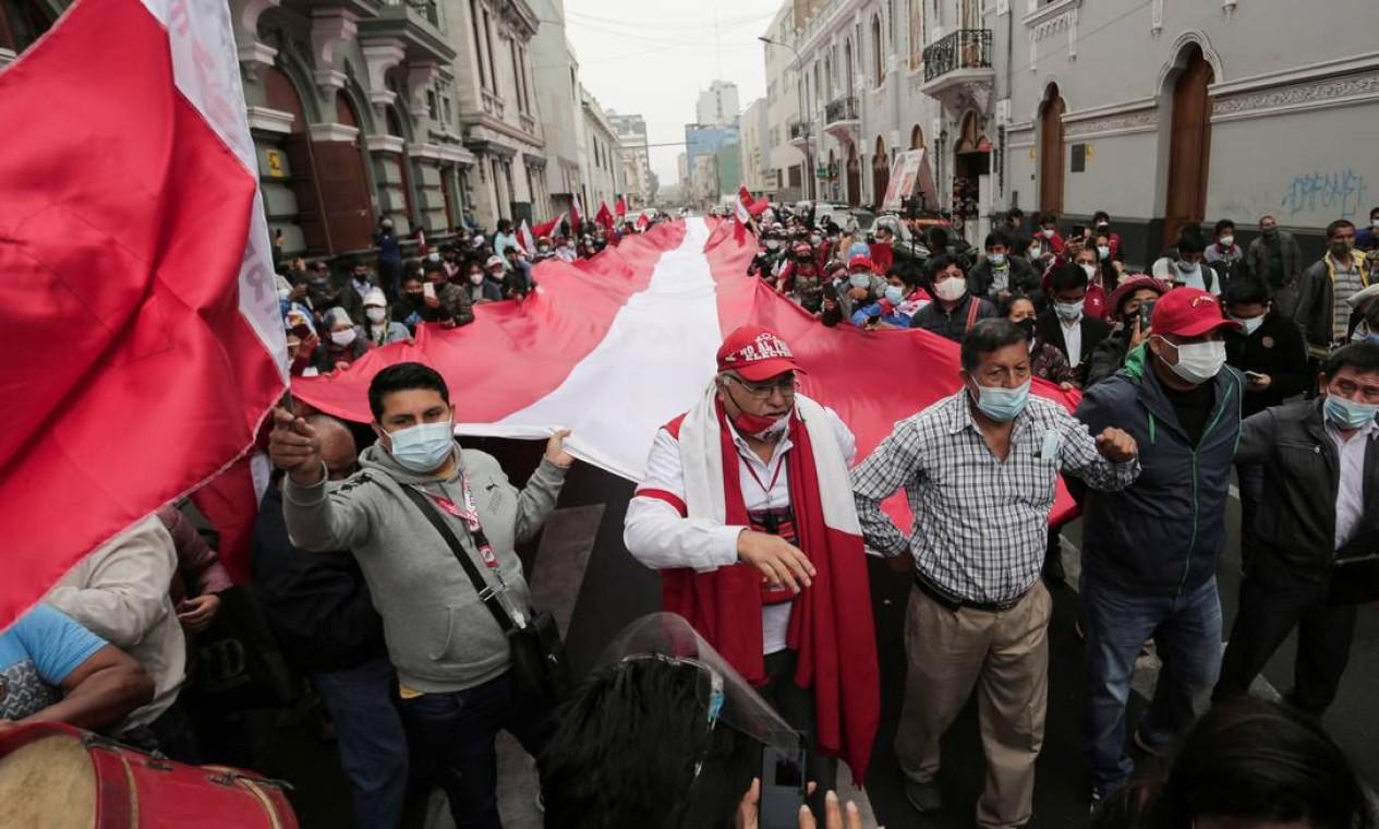 Apoiadores de Castillo marcham com bandeira gigante do Peru, na capital Lima Foto: STRINGER / REUTERS