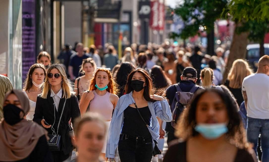 Pedestres, alguns usando máscaras faciais devido à Covid-19, passam por lojas na Oxford Street, no centro de Londres, em 7 de junho de 2021 Foto: NIKLAS HALLE'N / AFP